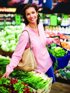 Portrait of beautiful woman buying vegetables in supermarket