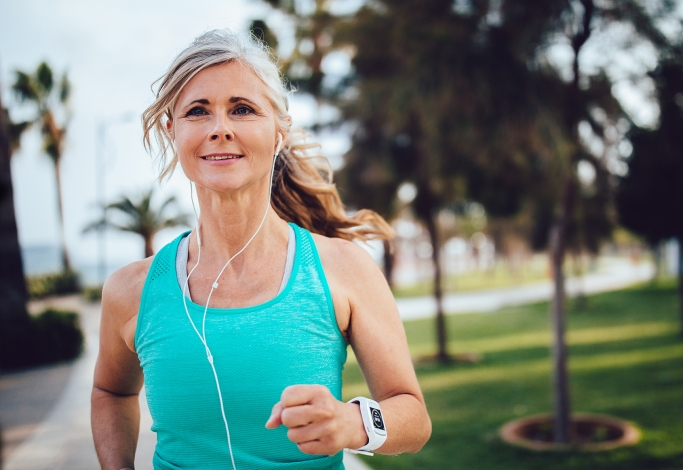 Active mature woman with headphones and smartwatch running in park